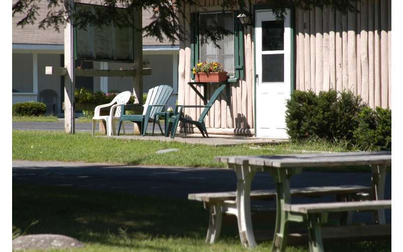 view of chairs and picnic table outside cabin