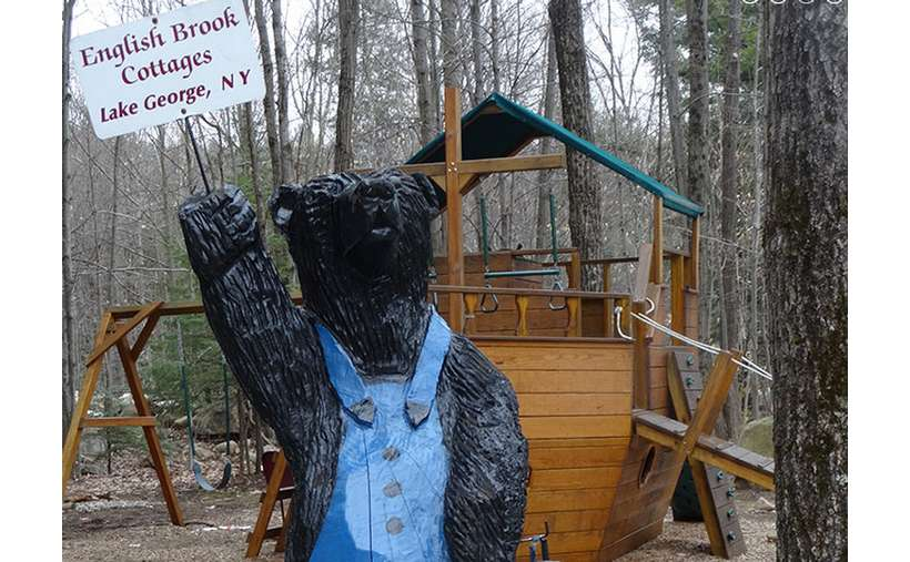 statue of a bear holding a sign saying English Brook Cottages