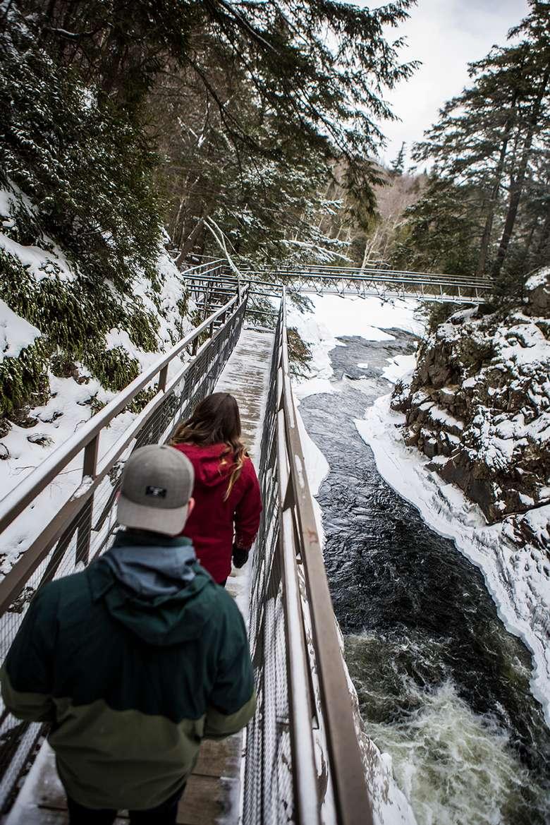 teenage boy and girl walking along the bridge in the winter