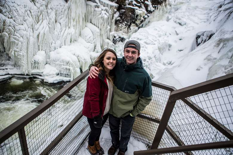 teenage boy and girl standing by waterfall in the wintertime