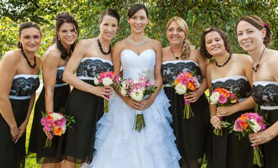 Bride with bridesmaids all holding pink and orange bouquets