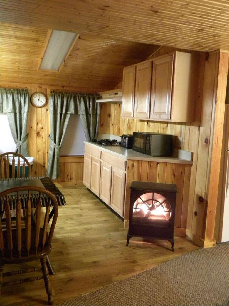 a small fireplace in a kitchen area inside a rustic cabin