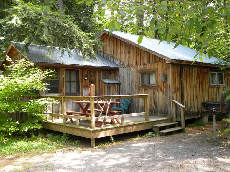 a light brown wooden cabin with a wooden deck