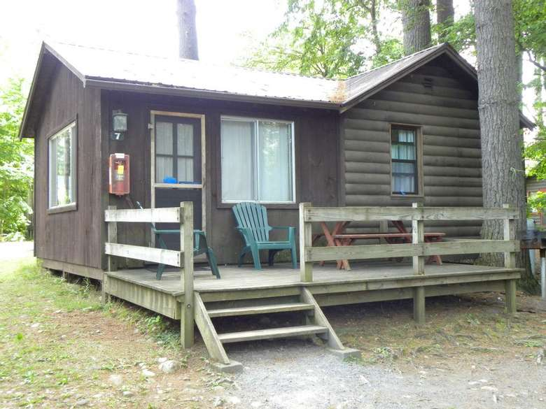 a dark brown cabin with a small wooden deck