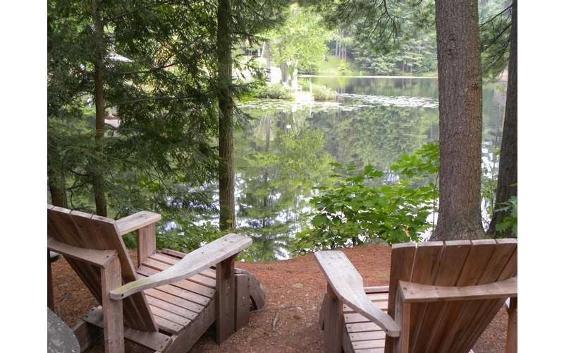 two wooden adirondack chairs facing a hidden lake