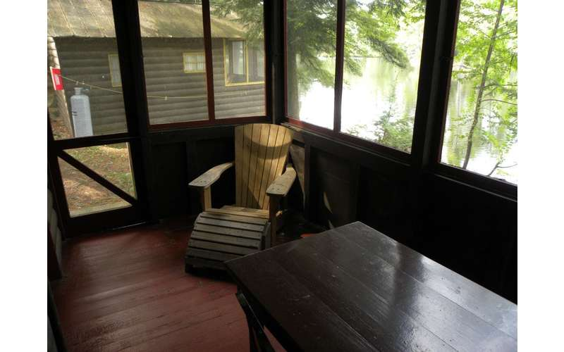 a screened-in porch with a chair and table