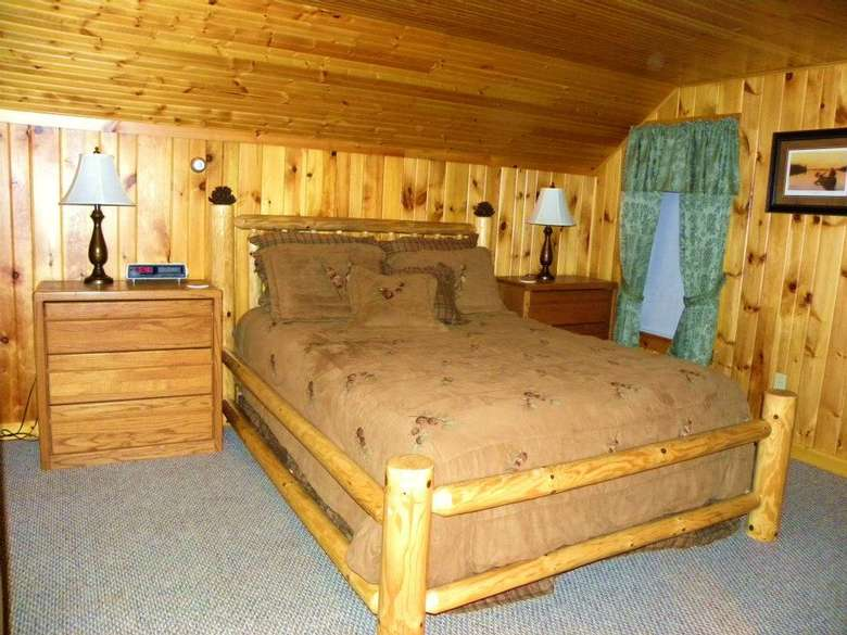 a rustic bedroom with a large bed and a dresser next to it