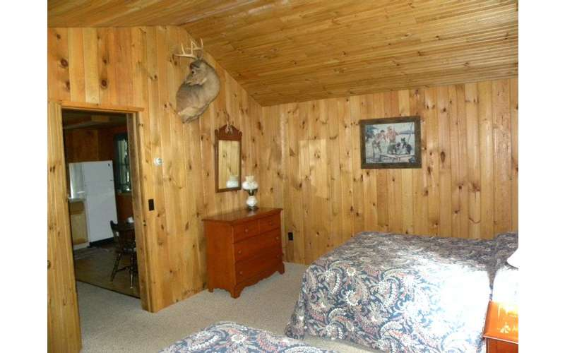 a rustic cabin room with two beds and a dresser