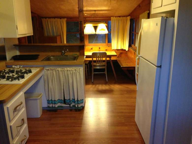 a kitchen area in a rustic cabin with a sitting area in the back