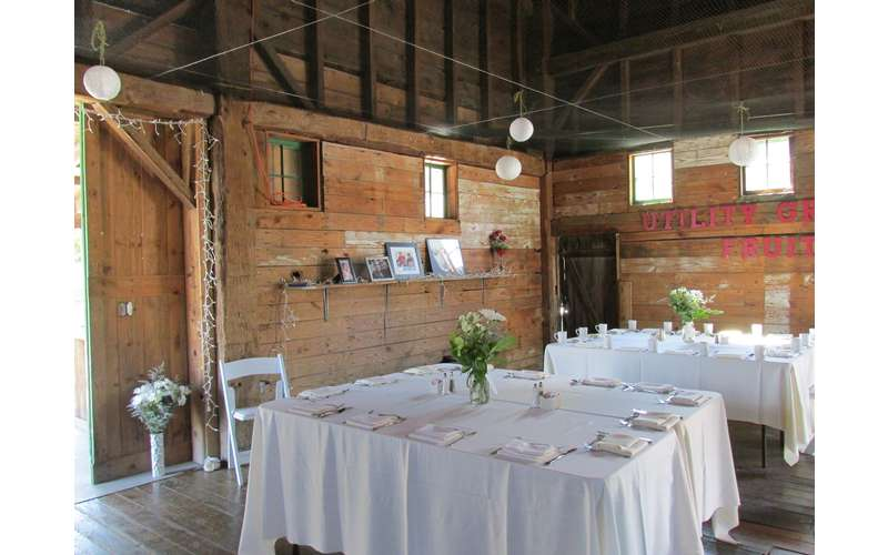 white tablecloths on tables in a barn wedding reception venue