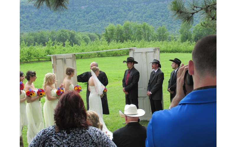 a wedding ceremony with scenic views of the green countryside