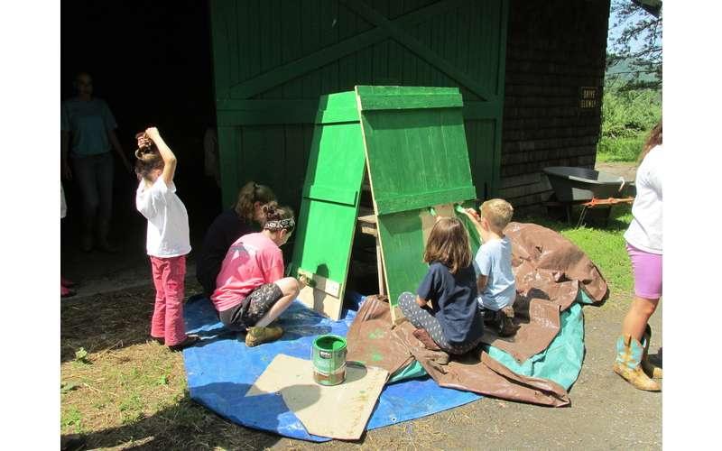 kids on a farm working on a fun painting project outdoors