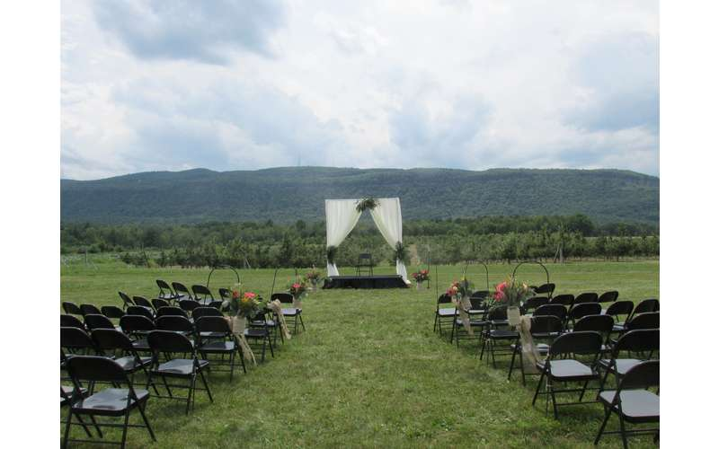 empty chairs set up in preparation for a wedding ceremony in the countryside with mountain views in the background