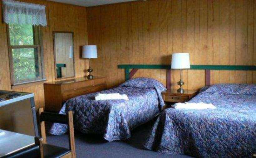 two beds in room with blue bedspread