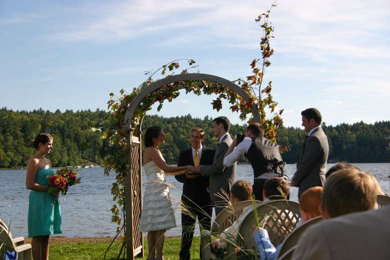 a couple getting married under an arch in front of the water