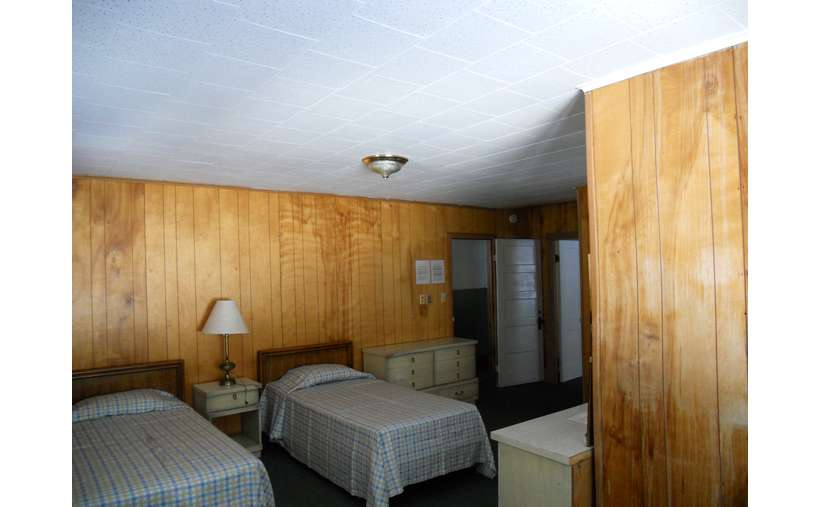 bedroom area with wood panel walls