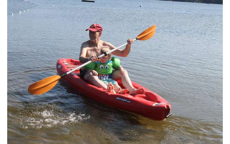 man kayaking with little boy in the boat