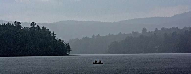 a grayish artsy photo of two people out in a boat on the lake