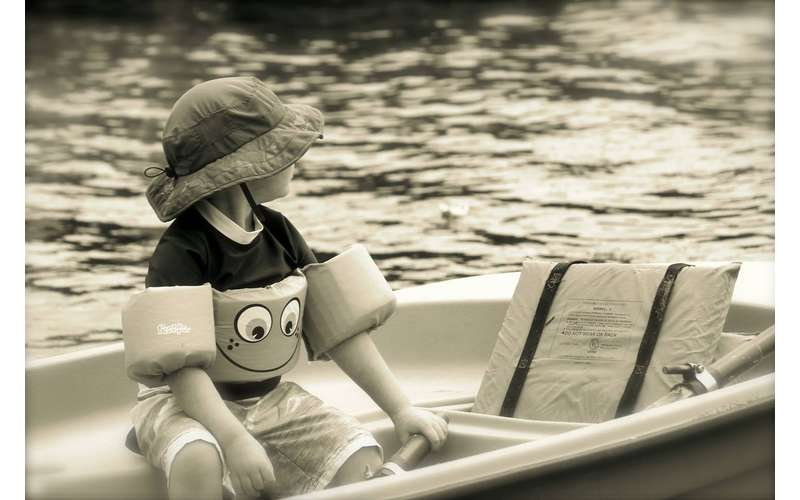black and white photo of a kid in a boat with swimmies