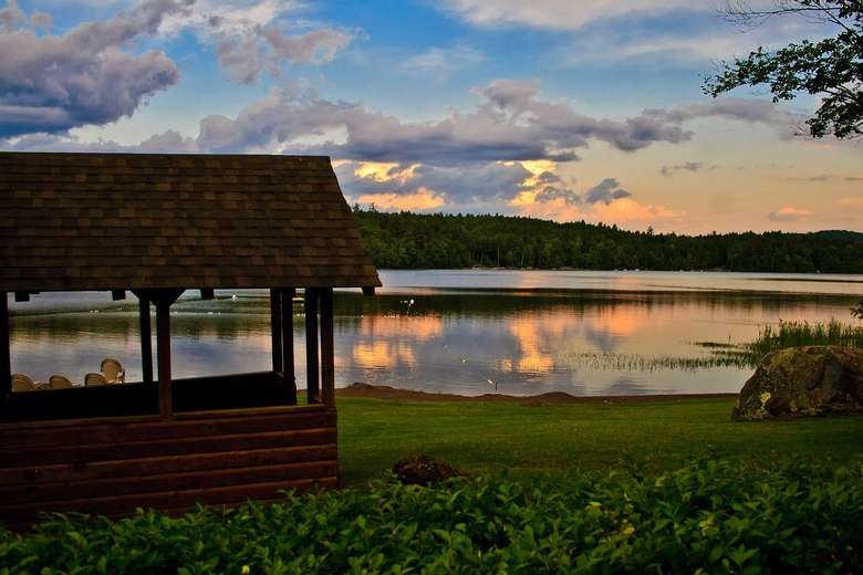 a wooden structure near the lake at sunset
