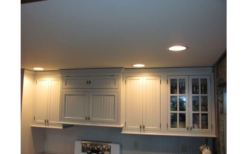 lights on the ceiling shining on upper kitchen cabinets