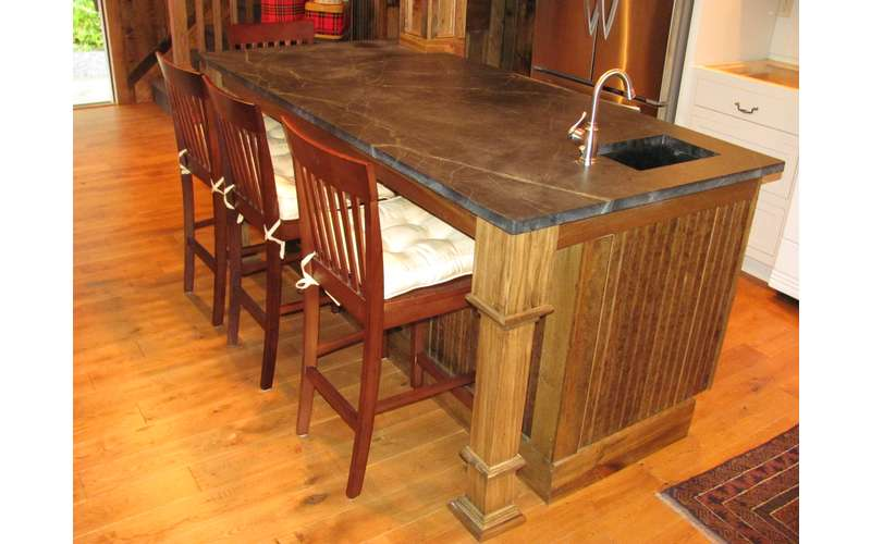 a wooden and rustic looking kitchen island with chairs around it