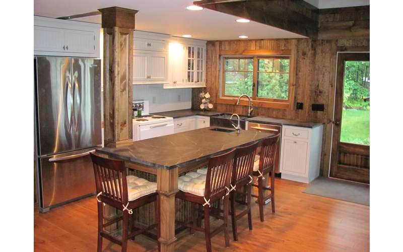 a kitchen island with chairs around it and a sink at one end