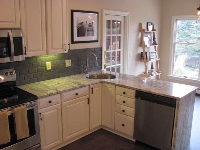 the corner of a kitchen cabinet space with a sink in the center