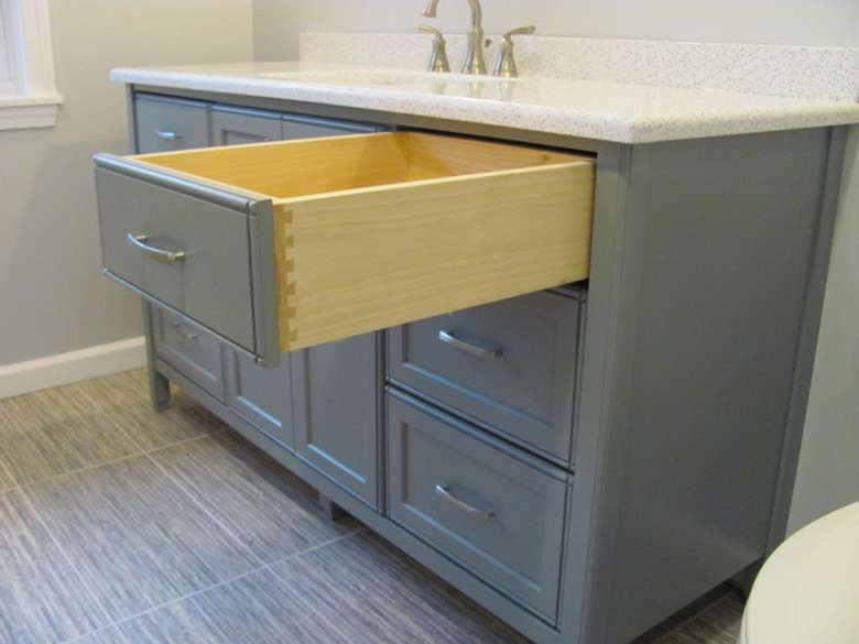 an off white bathroom cabinet with an open drawer