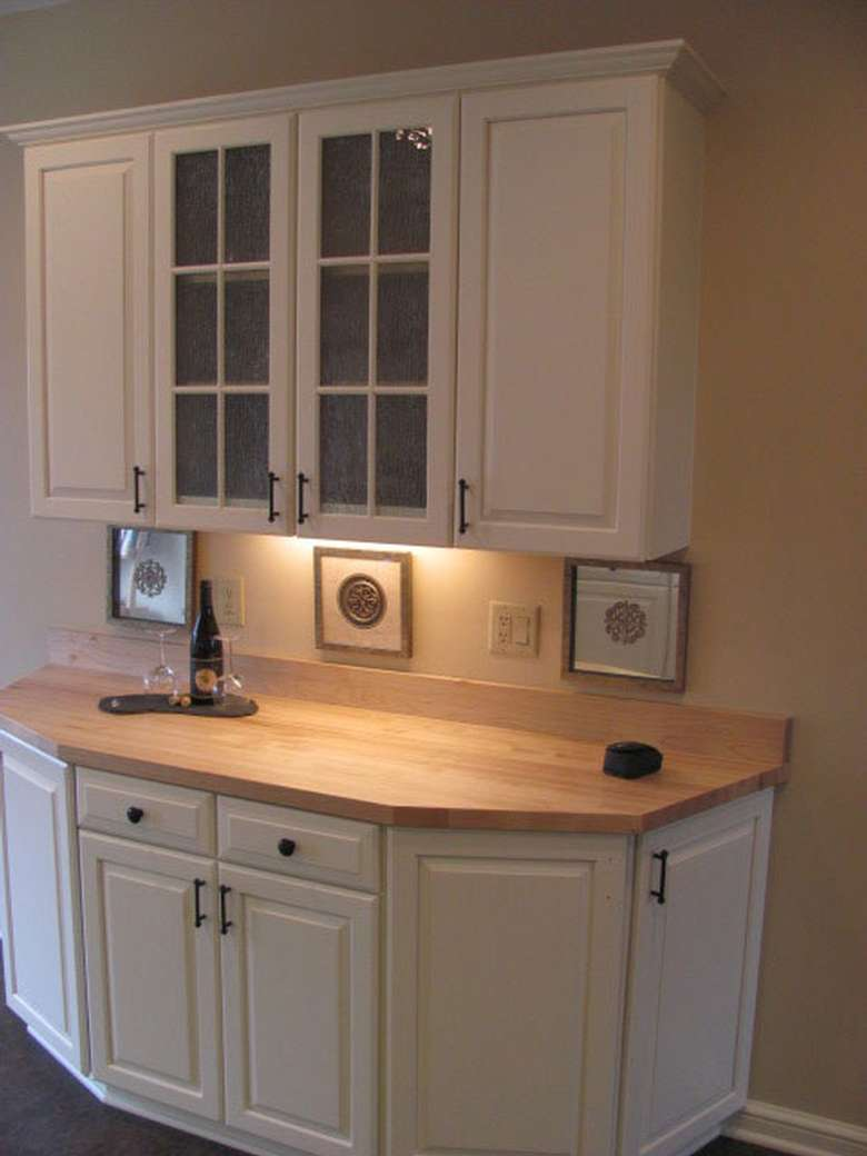 an upper and lower cabinet with lights attached below the upper one