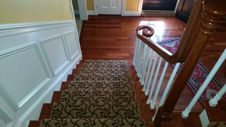 wood stairs with a runner, with white wainscoting to the left, and white rails with dark wood hand railing to the right.