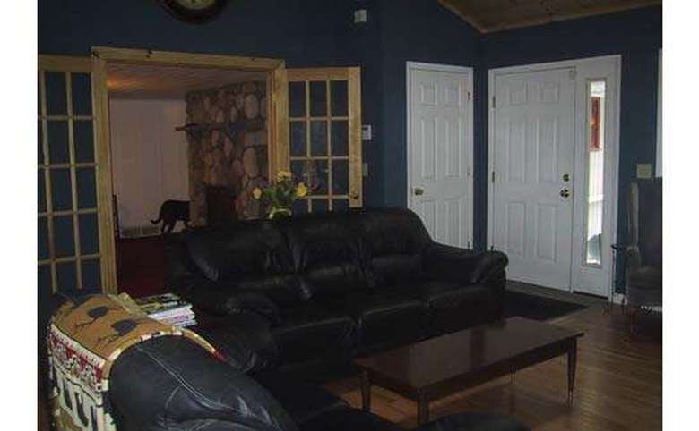 two black leather couches in a room with dark blue walls