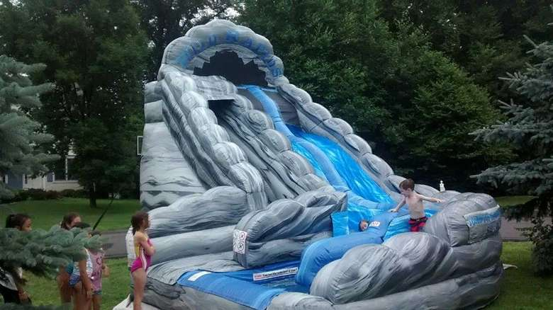 Kids sliding down an inflatable waterslide