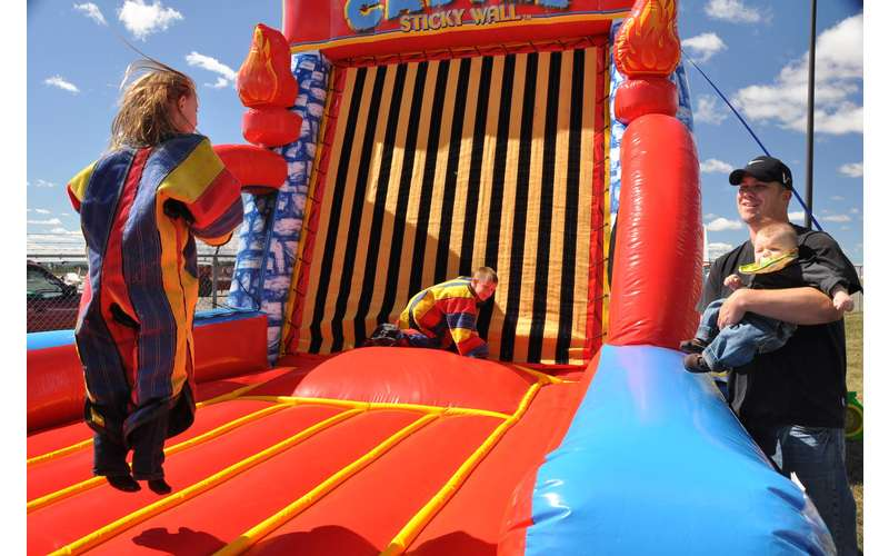 Kids jumping on an inflated sticky Velcro wall while their dad looks on