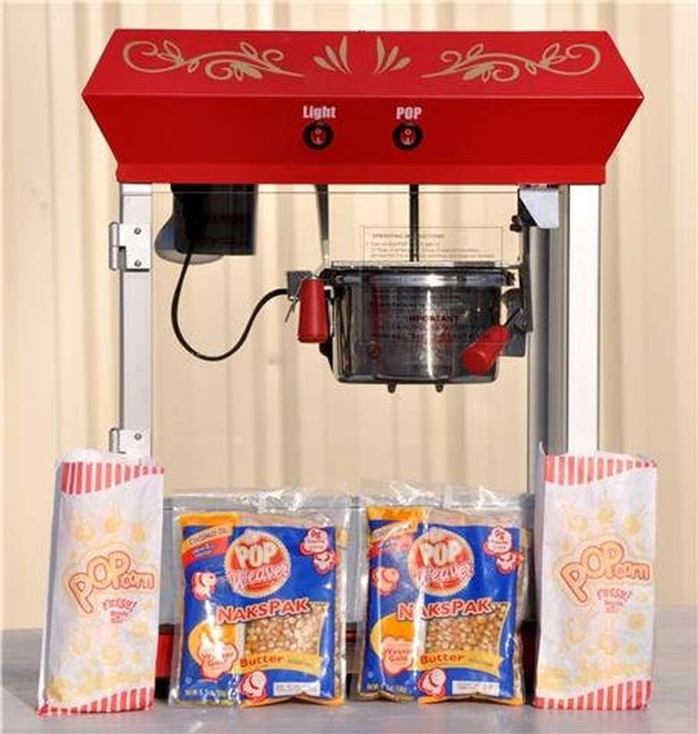 A popcorn maker with bags of corn