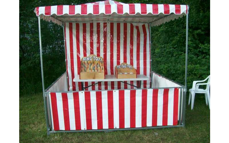A red and white striped booth with ring toss and tic-tac-toe games
