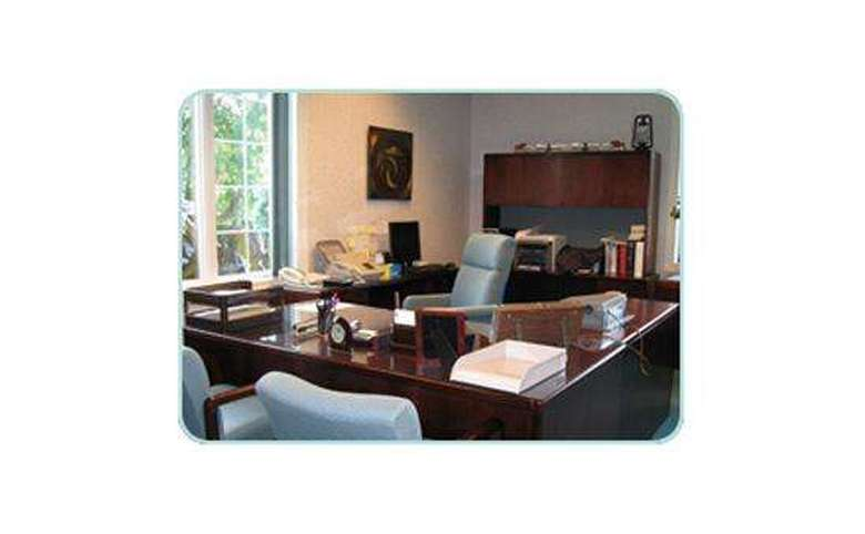 business person's office with a large desk and two chairs for guests