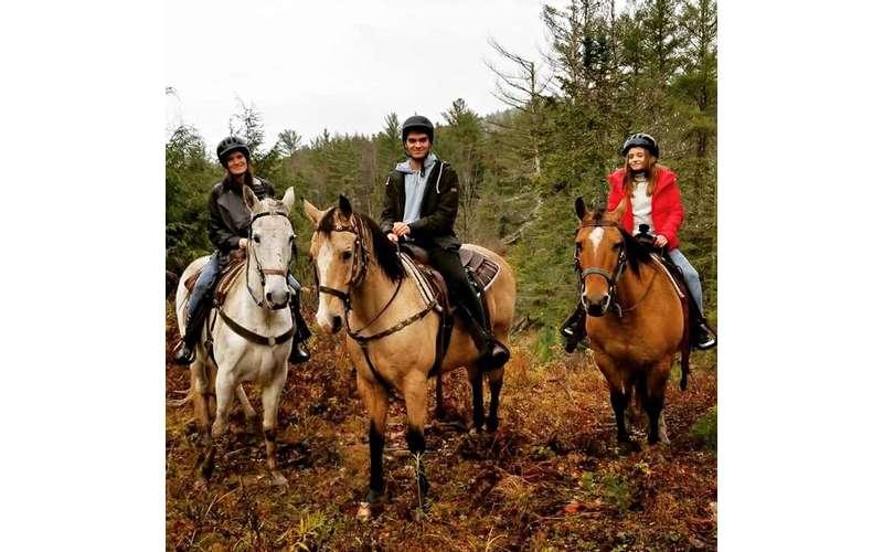 three people horseback riding