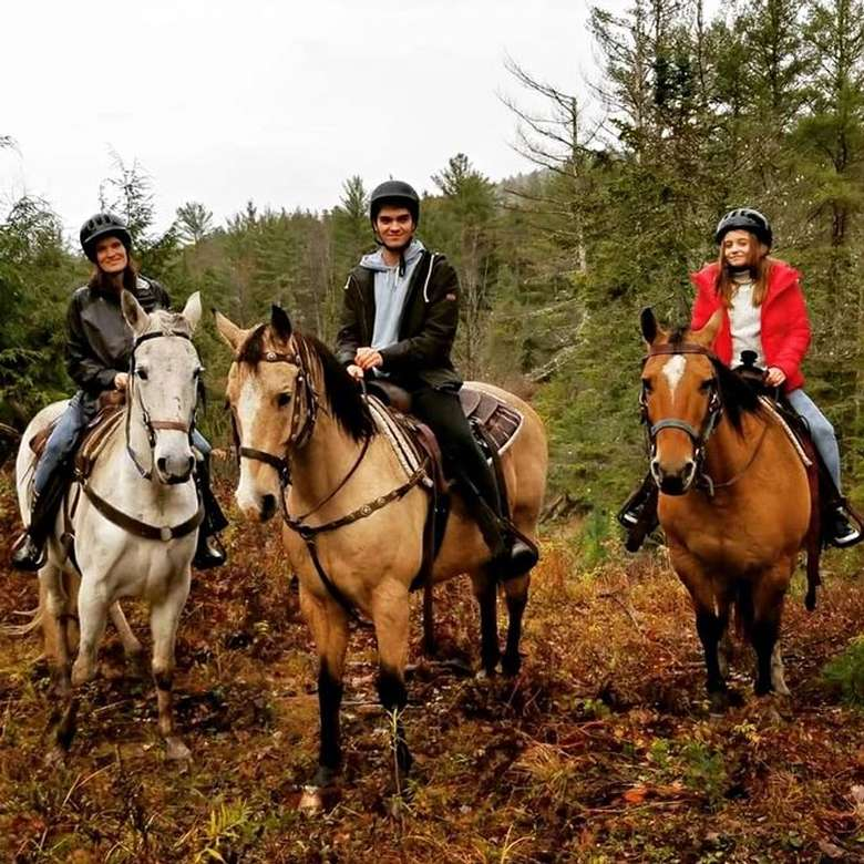 three people horseback riding