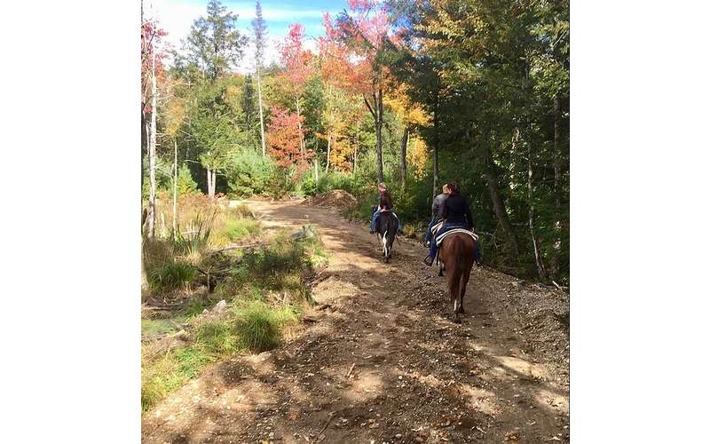 three people horseback riding in autumn