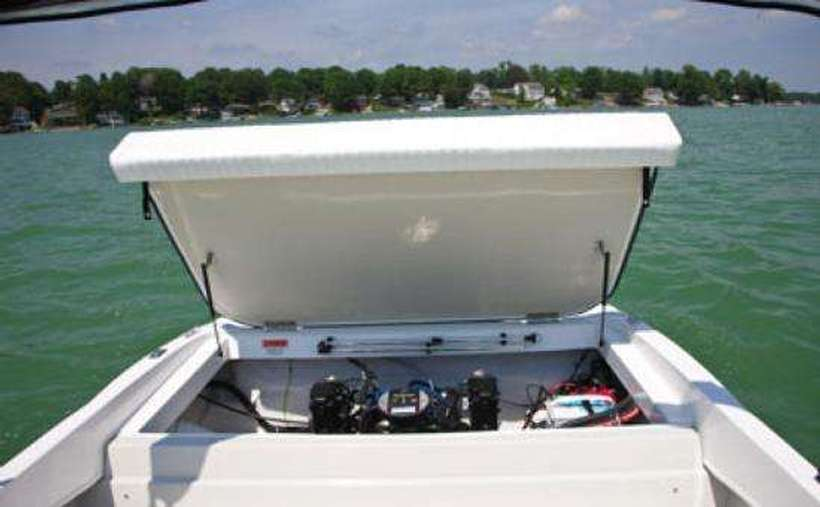 an open compartment on a boat showing the motor