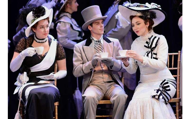 three people on stage in Victorian clothing having tea