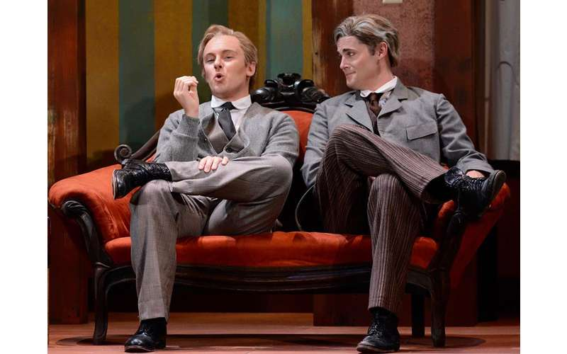 two men in suits on stage sitting on a couch