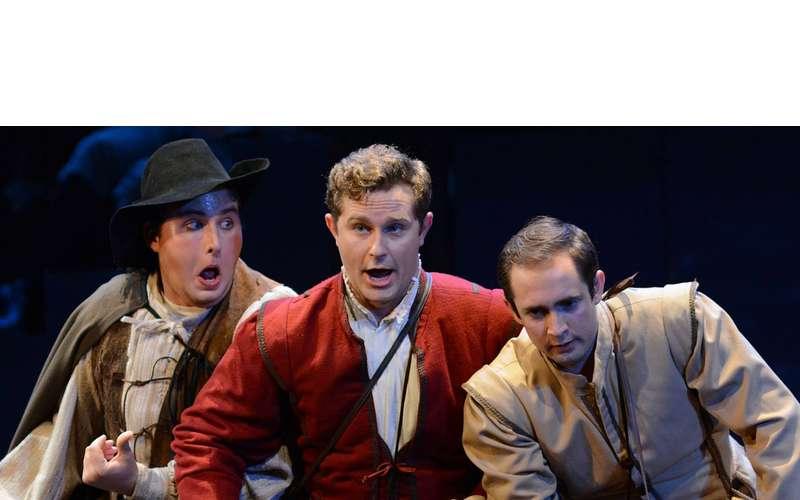 three men on stage singing