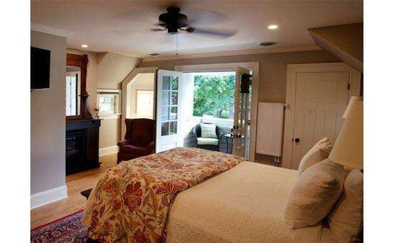 bedroom at an inn with a queen size bed and a ceiling fan