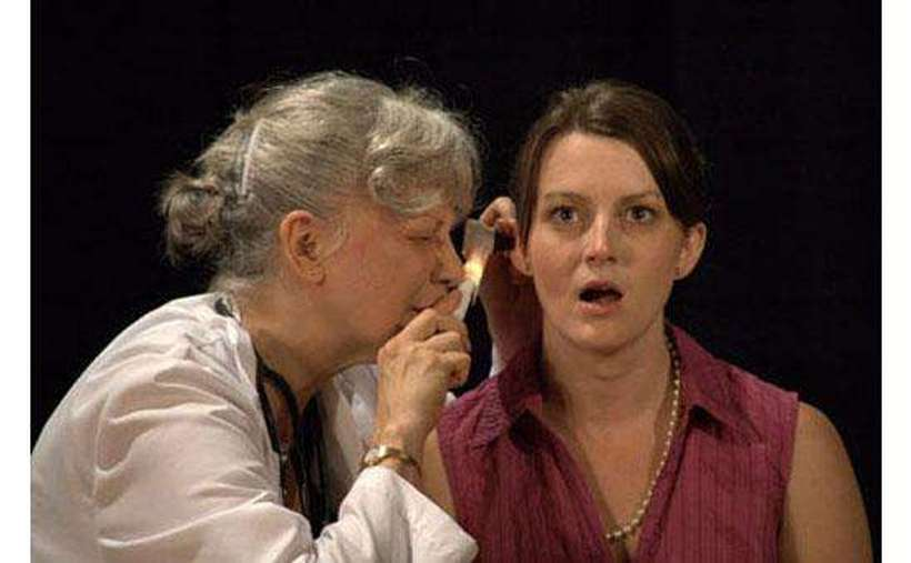 Two actresses, one of whom is dressed like a doctor and examining the other's ear