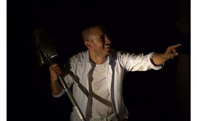 An actor pointing in near darkness