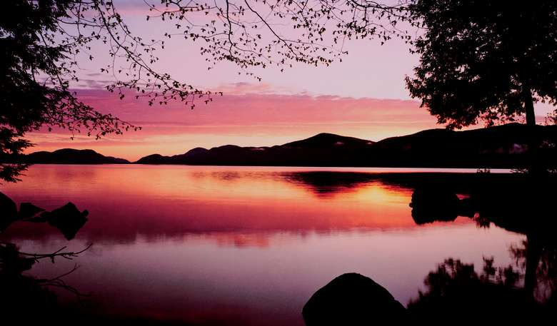 a beautiful pink and orange sunset on lake george, reflected in the water