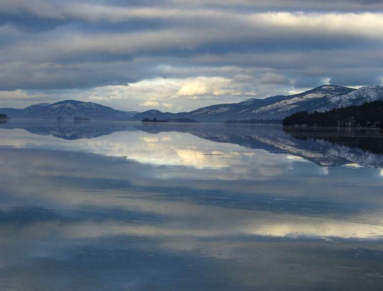 lake george in the winter with clouds reflected in the water and a sprinkling of snow on the mountains