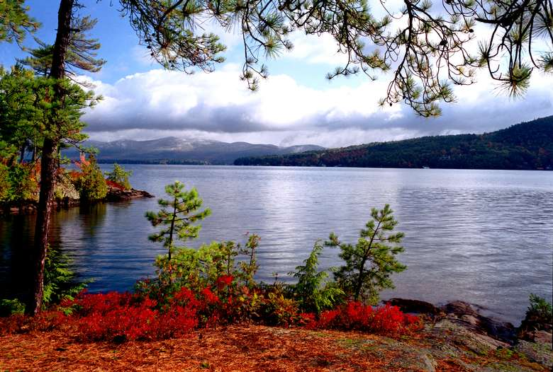 lake george in the early fall with some red and gold foliage, the lake, and mountains in the background